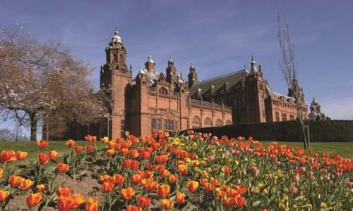 Exterior view of Kelvingrove Art Gallery & Museum with red and yellow flowers in the foreground