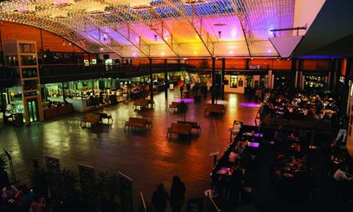Large indoor courtyard space surrounded by restaurants and bars with fairy lights on the roof