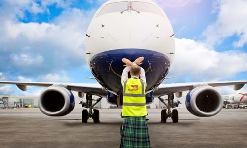The back of a man standing in front of a plane dressed in a kilt and high visibility vest which has People Make Glasgow written on the back