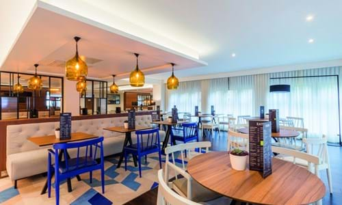 Bright dining area with wooden tables and blue and white chairs