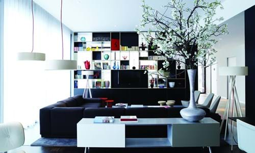 Modern lounge area with black corner couch and a shelving wall featuring decorative items such as books