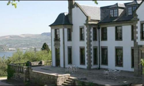 Exterior of country house hotel set within gardens with views across water