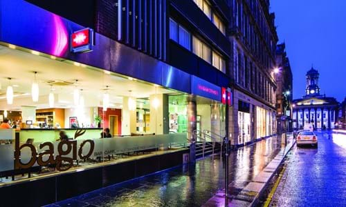 Exterior street view of the Mercure hotel in Glasgow in the evening rain