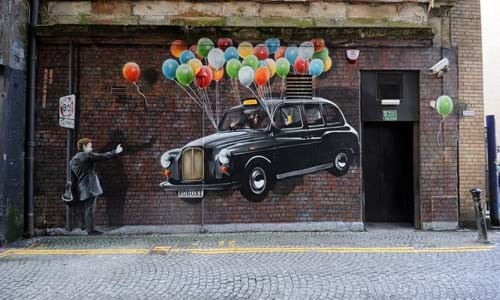 Glasgow street art mural of a floating taxi with balloons