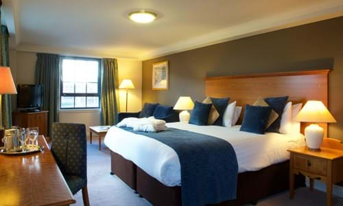 Hotel bedroom with large bed seating area and desk