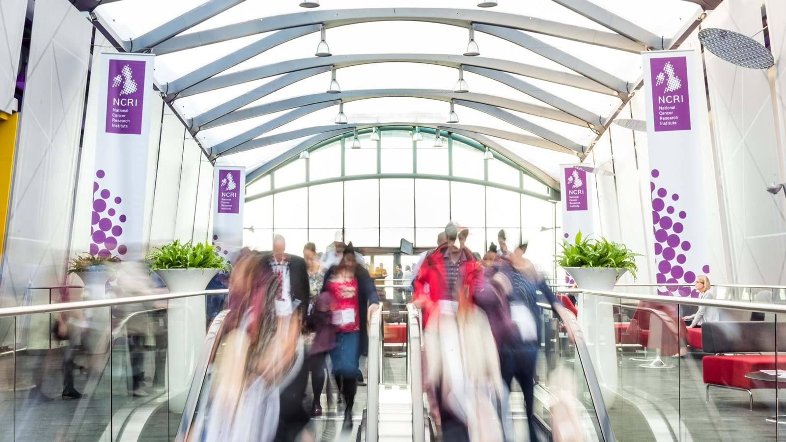 Blurred image of delegates travelling down escalators during the NCRI conference