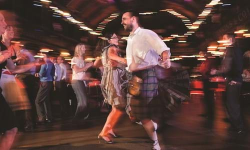 Delegates enjoying ceilidh dancing with a man wearing a kilt in the Old Fruitmarket in Glasgow