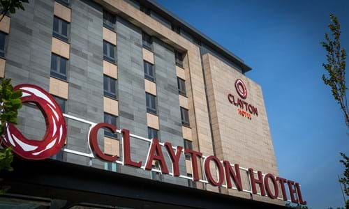Exterior hotel sign which reads 'Clayton Hotel' with the building visible in the background