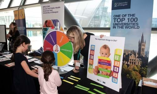 Children speaking to a team member and engaging with a display at the Glasgow Science Centre Obesity Event