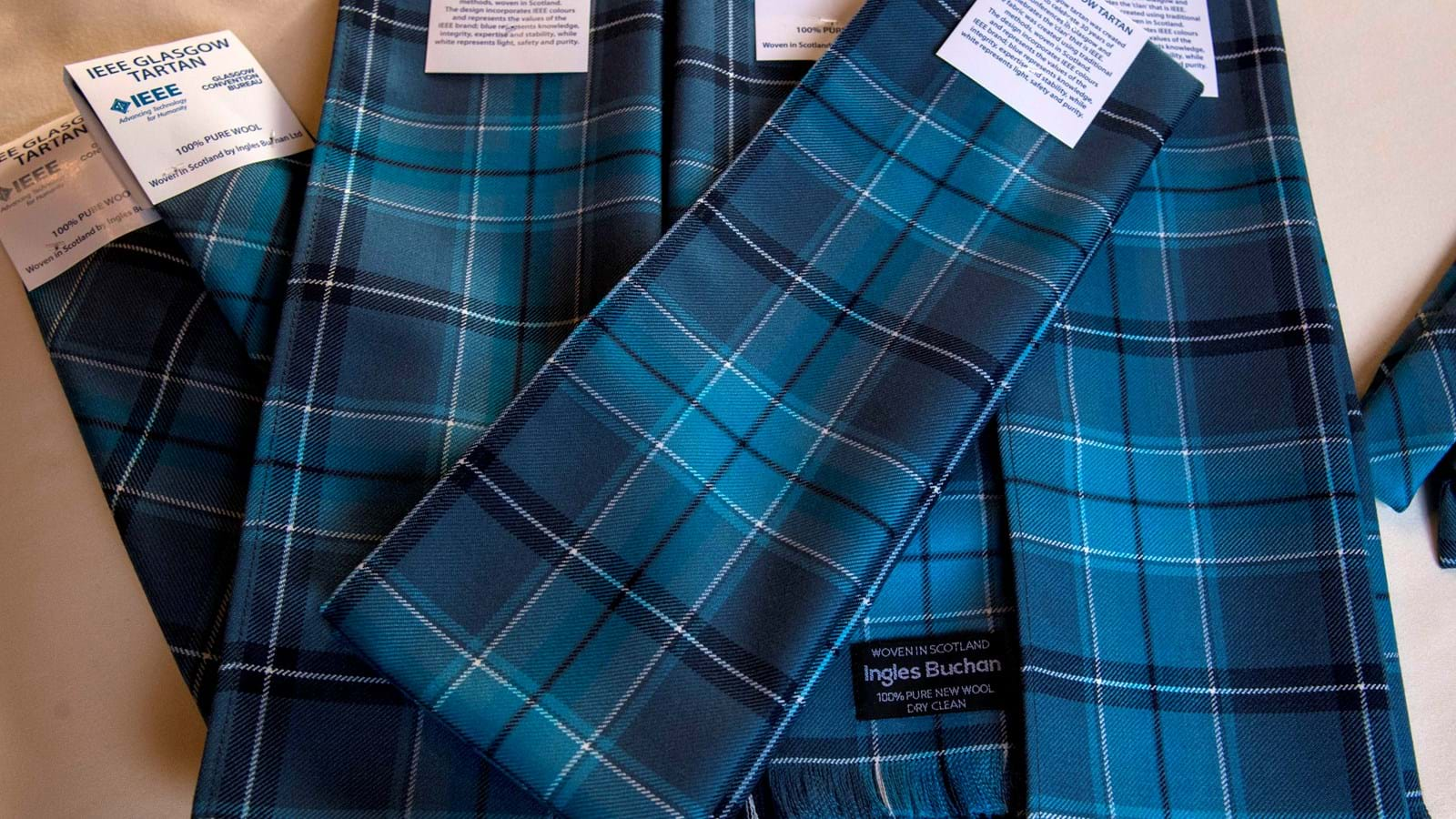 A selection of ties and sashes in the IEEE Glasgow tartan arranged on a table