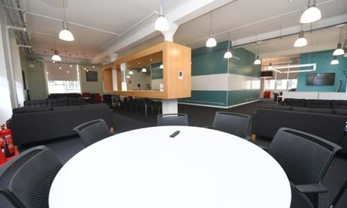 White round table with overview of open plan meeting space in the background
