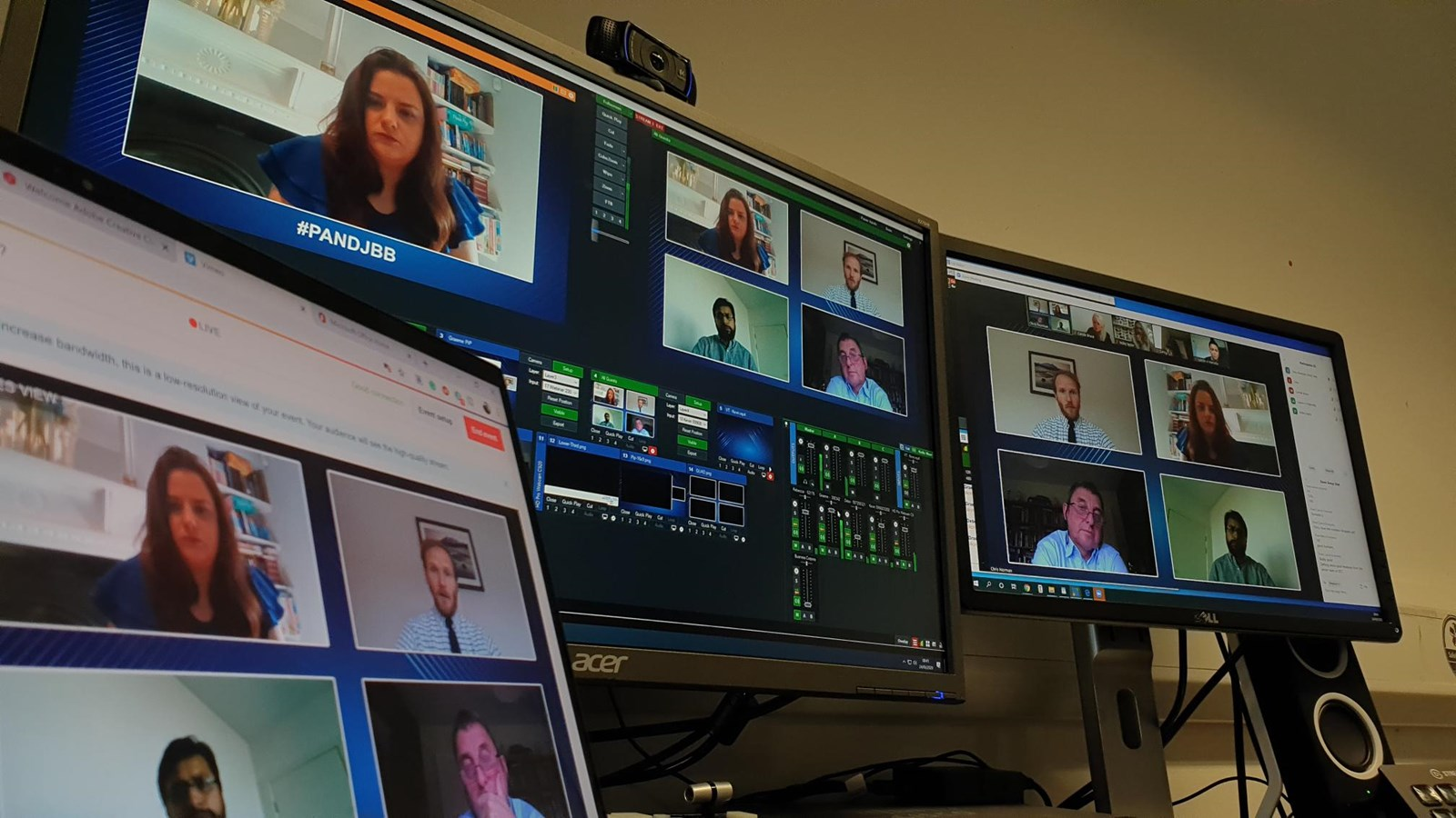 Three large computer screens displaying an online video meeting